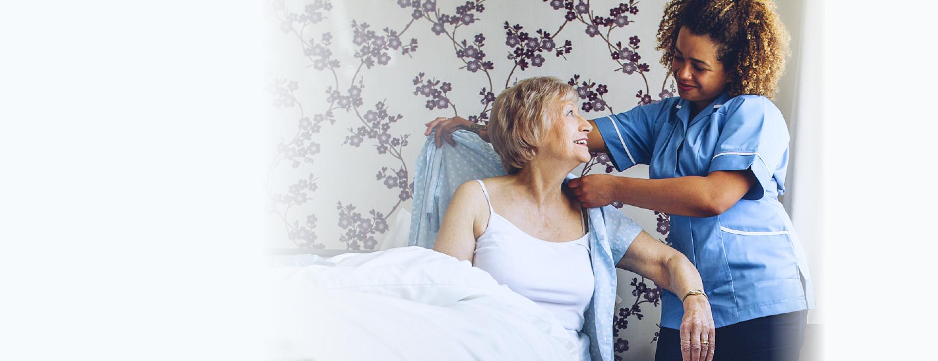 home caregiver dressing the senior woman