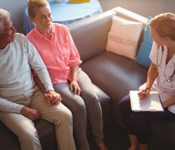 elderly couple and nurse talking