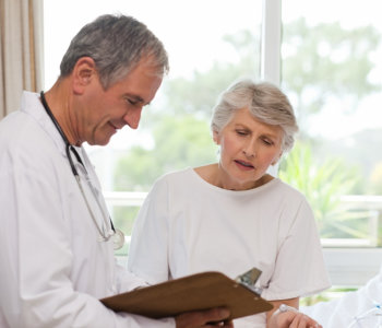 doctor and elder woman looking to the record sheet
