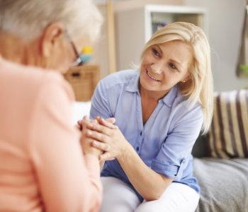 caregiver comforting elder woman